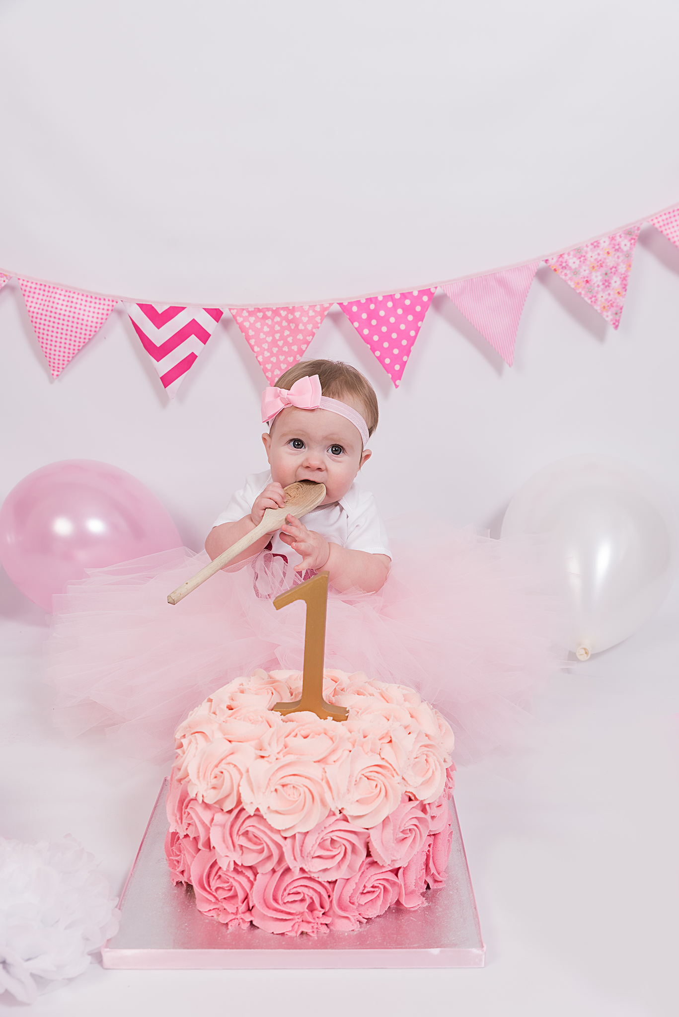388dd2bd2 Cake smash photographer Crawley. girl sitting down with a wooden spoon in  her hand and