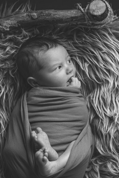Baby photographer Surrey, newborn baby boy in a wrap with feet showing laying on his back on a wooden log bed facing away from camera