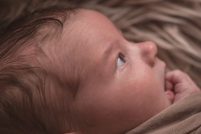 newborn photographer sussex, close up of newborn baby boy's face. Side view with his eye being the main focus