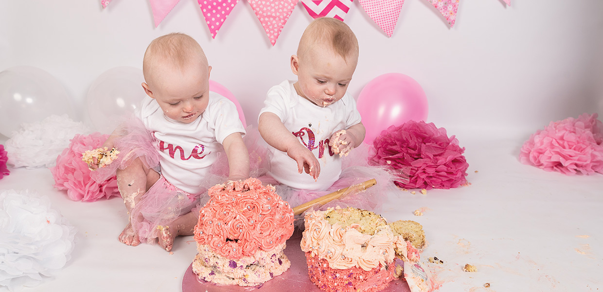 twin girls sitting on floor with pink bunting in the background and 2 giant cupcakes in front of them getting ready to smash the cake. Cake smash photography