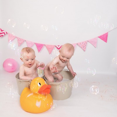 Cake smash and splash, twin girls in metal bath tin (one each) looking at a giant rubber duck yellow in colour