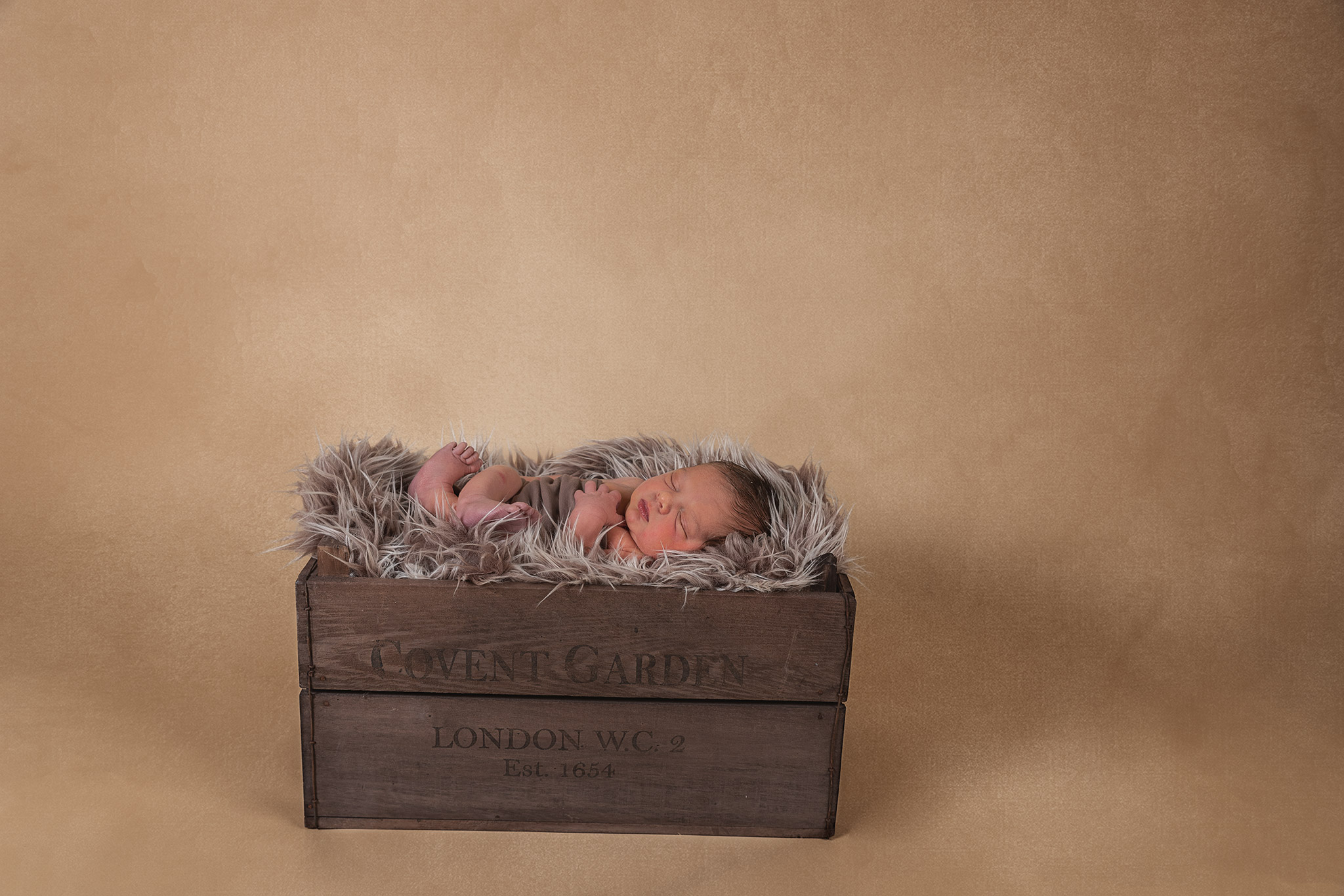 Brown fury blanket in a Brown wooden crate with a newborn baby boy laying on his back wrapped in a brown fabric with feet and arms showing. Baby is sleeping and the background is beige