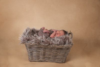 Brown fury blanket in a wicker basket with a newborn baby boy laying on his back wrapped in a brown fabric with feet showing. Baby is sleeping and the background is Beige