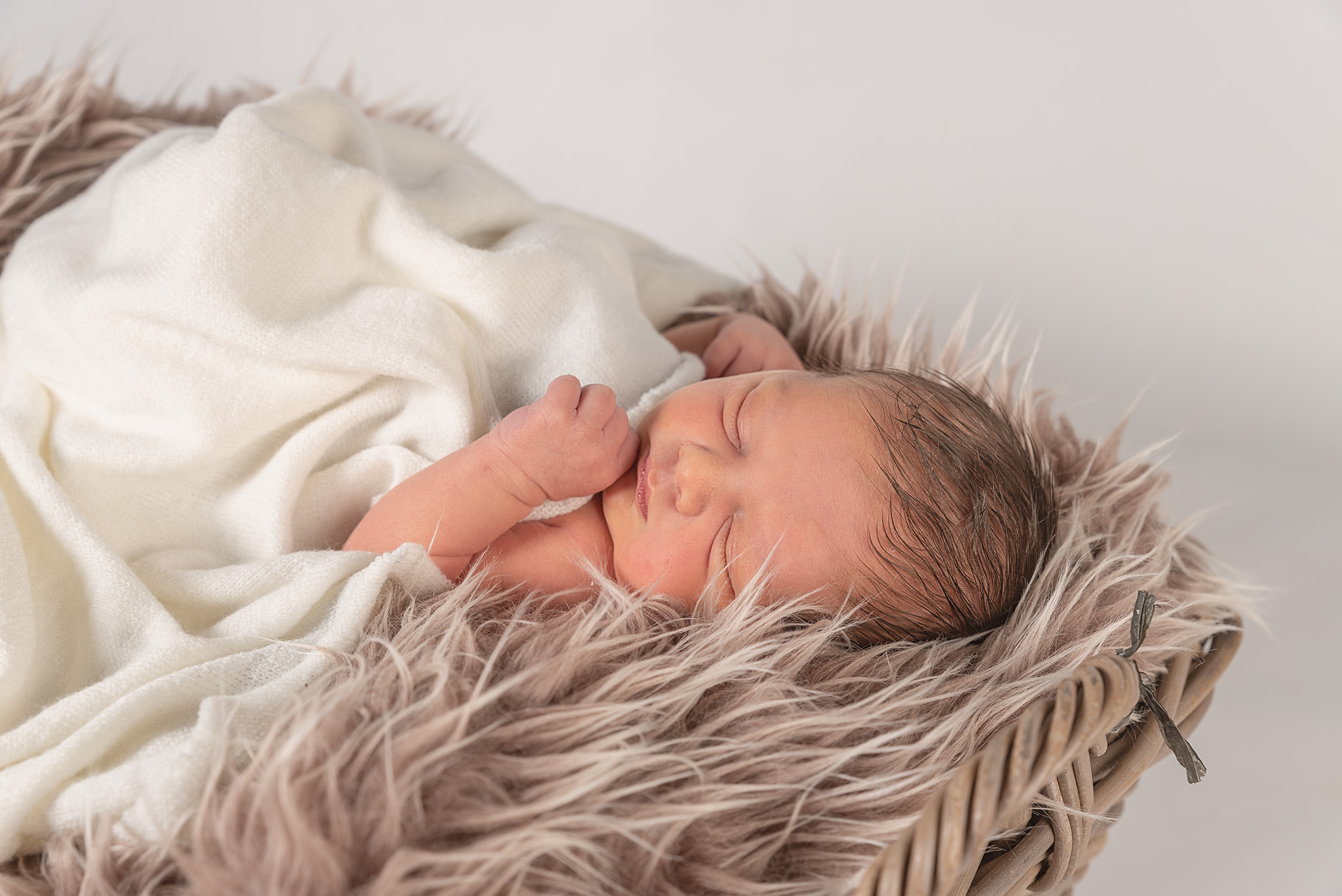 close up image of Newborn baby laying on his back with his fist on chin. Baby is laying in a wicker basket with a brown fury blanket and a white fabric covering his body