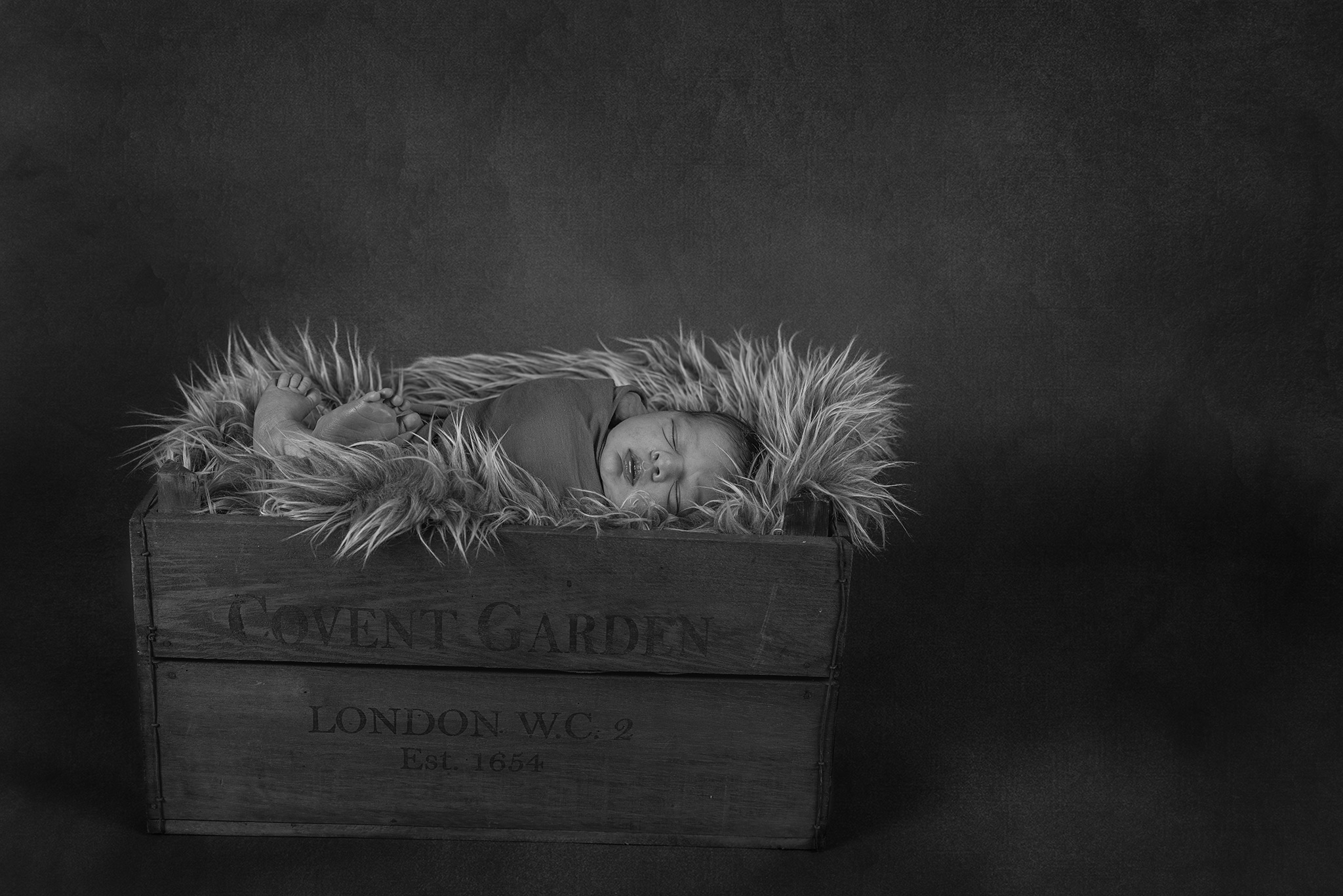 Newborn photography Burgess Hill. Black and white photo of baby wrapped in a fabric laying on his side in a wooden crate and a fury blanket.
