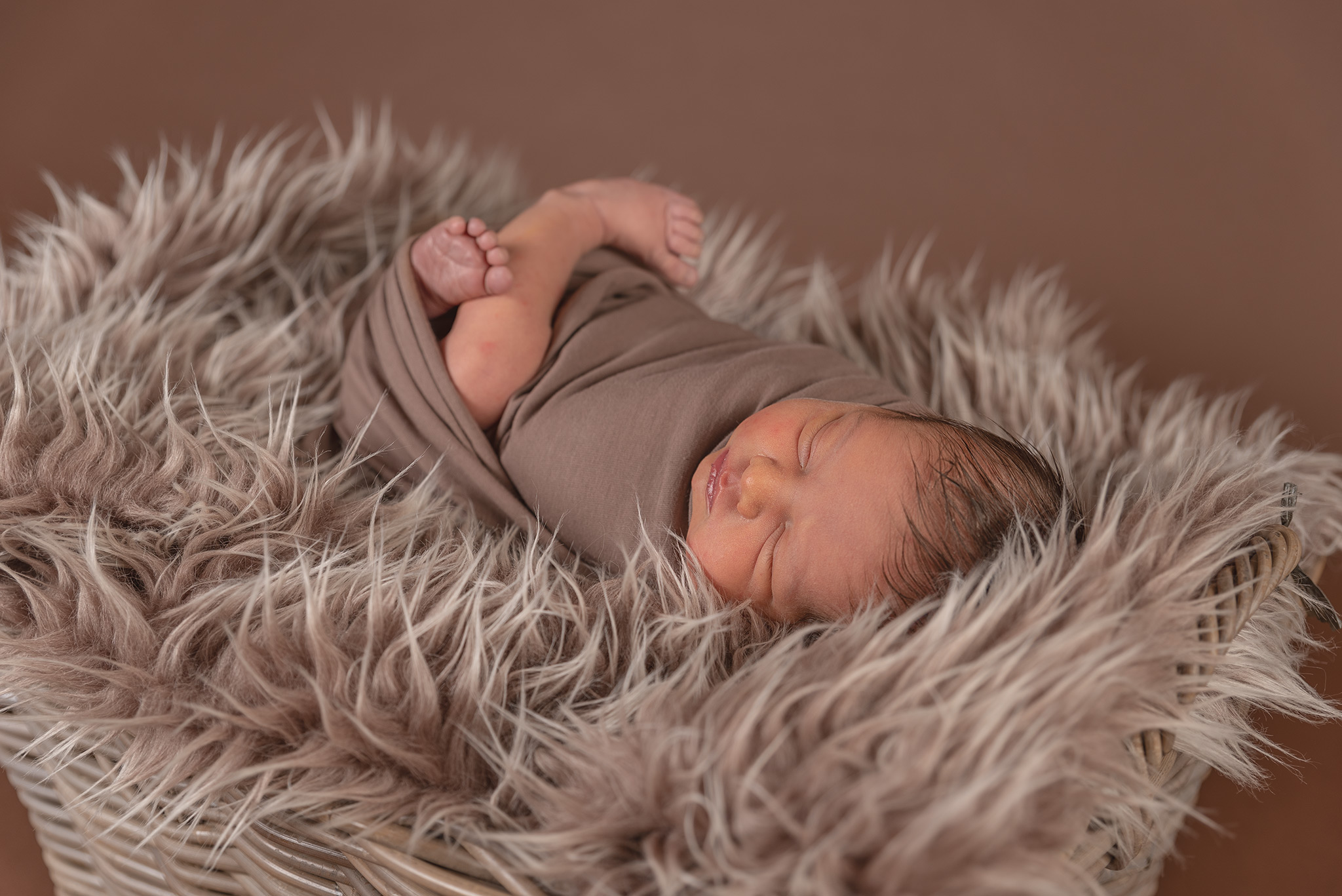 Brown fury blanket in a wicker basket with a newborn baby boy laying on his back wrapped in a brown fabric with feet showing. Baby is sleeping and the background is brown