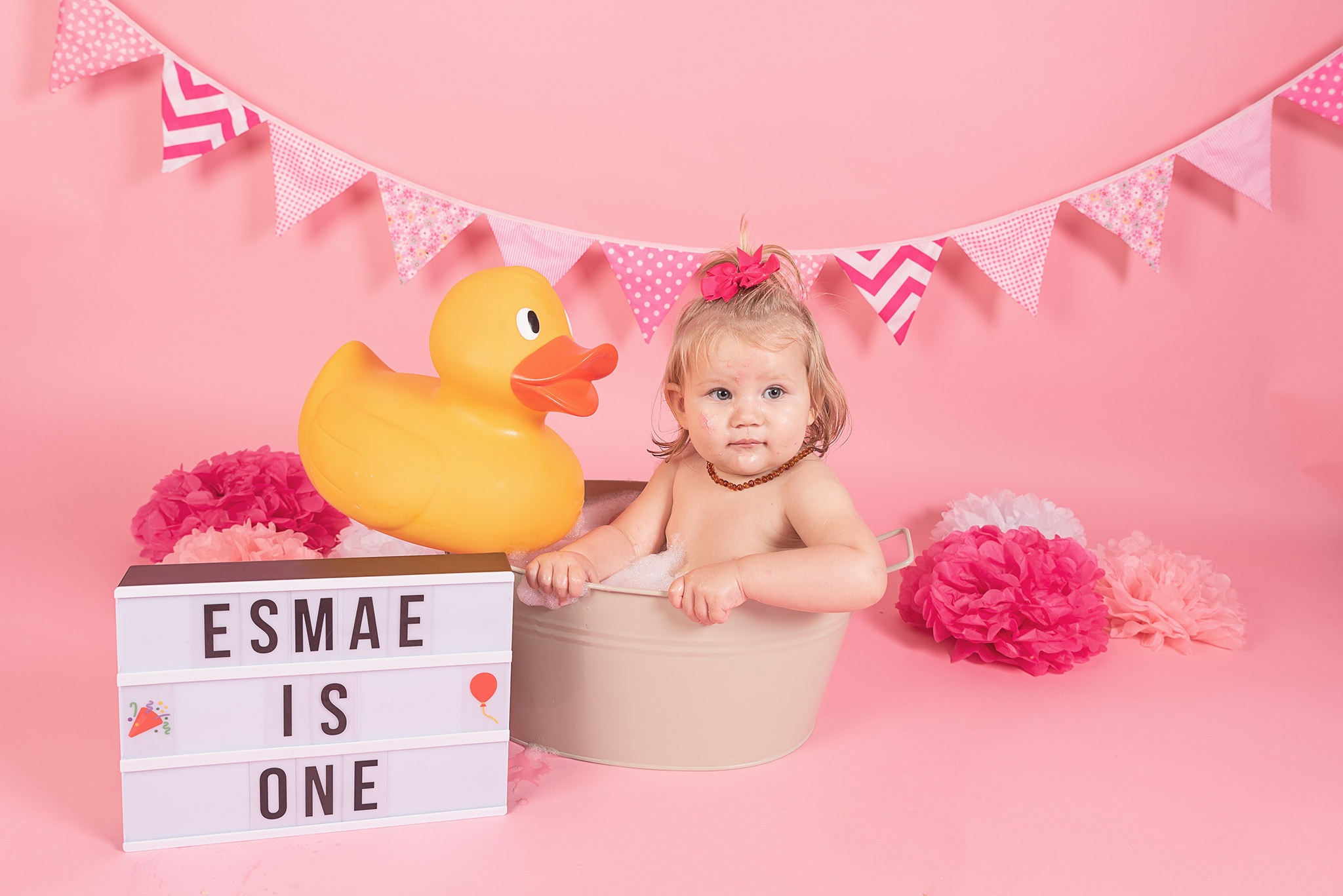 Cake smash photography Crawley. Girl in a metal bath tub cream in colour with a giant rubber duck on the edge. Name board that says Esmae is one.